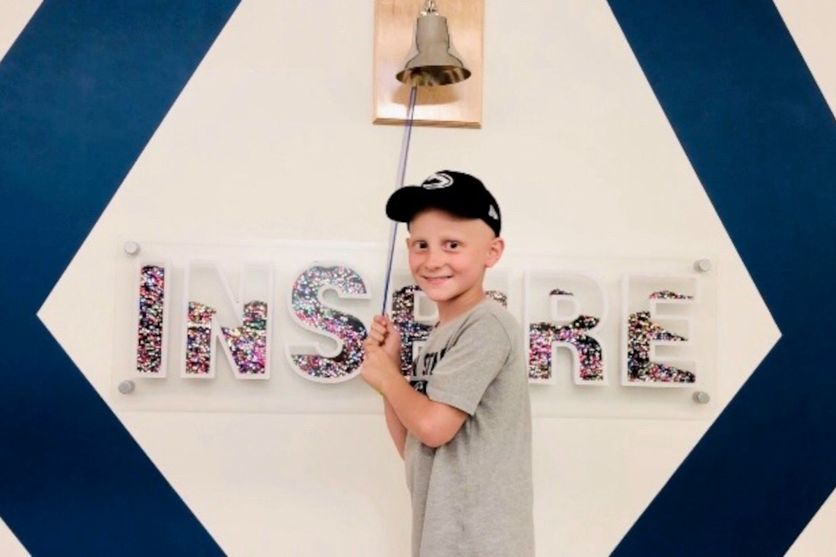 A boy wearing a baseball cap faces the camera and smiles, standing in front of a bell that hangs on a wall along with the word