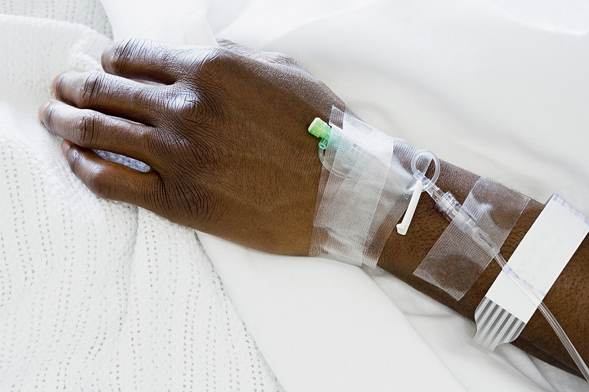 Close-up of a wrist and hand into which an IV line is inserted. Medical tape is on the arm, securing the line in place.