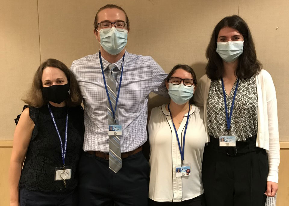 1 man and 3 women are standing in a line with their arms around each other's shoulders. They are all wearing face masks.