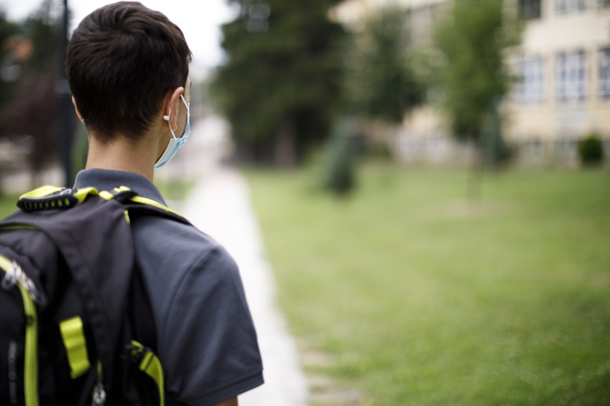 Rear view of school teenage boy with face protective mask in front of the school.