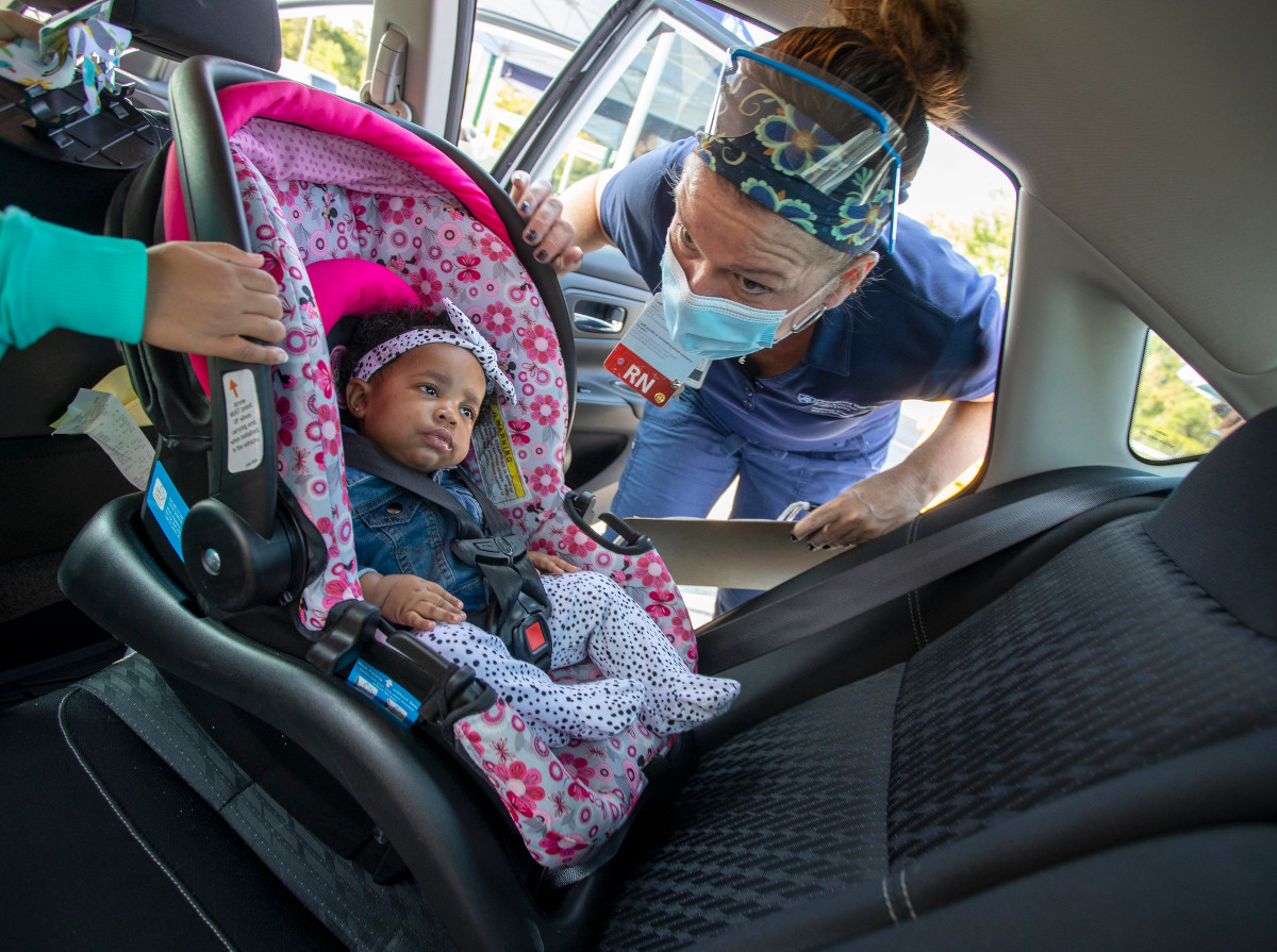 A woman checks a baby's car seat