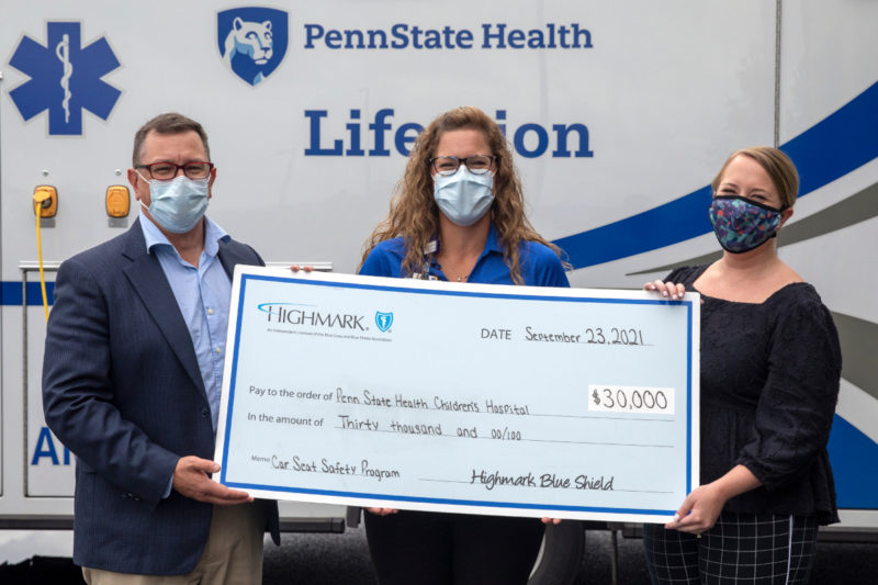 Three people smile while holding a big check