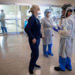 A care team dressed in full personal protective equipment meets outside of a hospital patient room