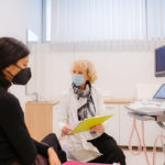 Doctor and patient with protective face masks during the medical examination