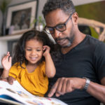 A man holds his young daughter on his lap as they both look down at a picture storybook. A bookshelf, artwork and plants are in the background.