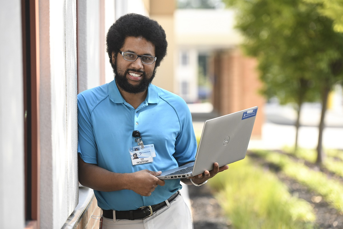 Penn State Health Information Services senior support specialist Sean Dolphin smiles as he leans against a wall outdoors. He is holding a laptop open. He has curly hair and a beard and is wearing glasses, a polo shirt and a nametag. Behind him are trees.