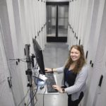 Lea Eller, a cyber defense infrastructure engineer at Penn State Health, stands in the middle of two rows of servers that are behind tall metal doors. She is standing at a laptop with her hands on the keyboard and looking up and smiling. She has long, curly hair and is wearing a top, long-sleeved sweater and nametag with a lanyard.