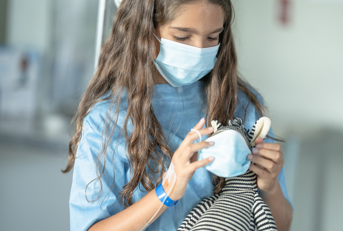 A young girl is putting on a doll face mask onto her zebra teddy bear. She is also wearing a face mask at the hospital to prevent the spread of germs.