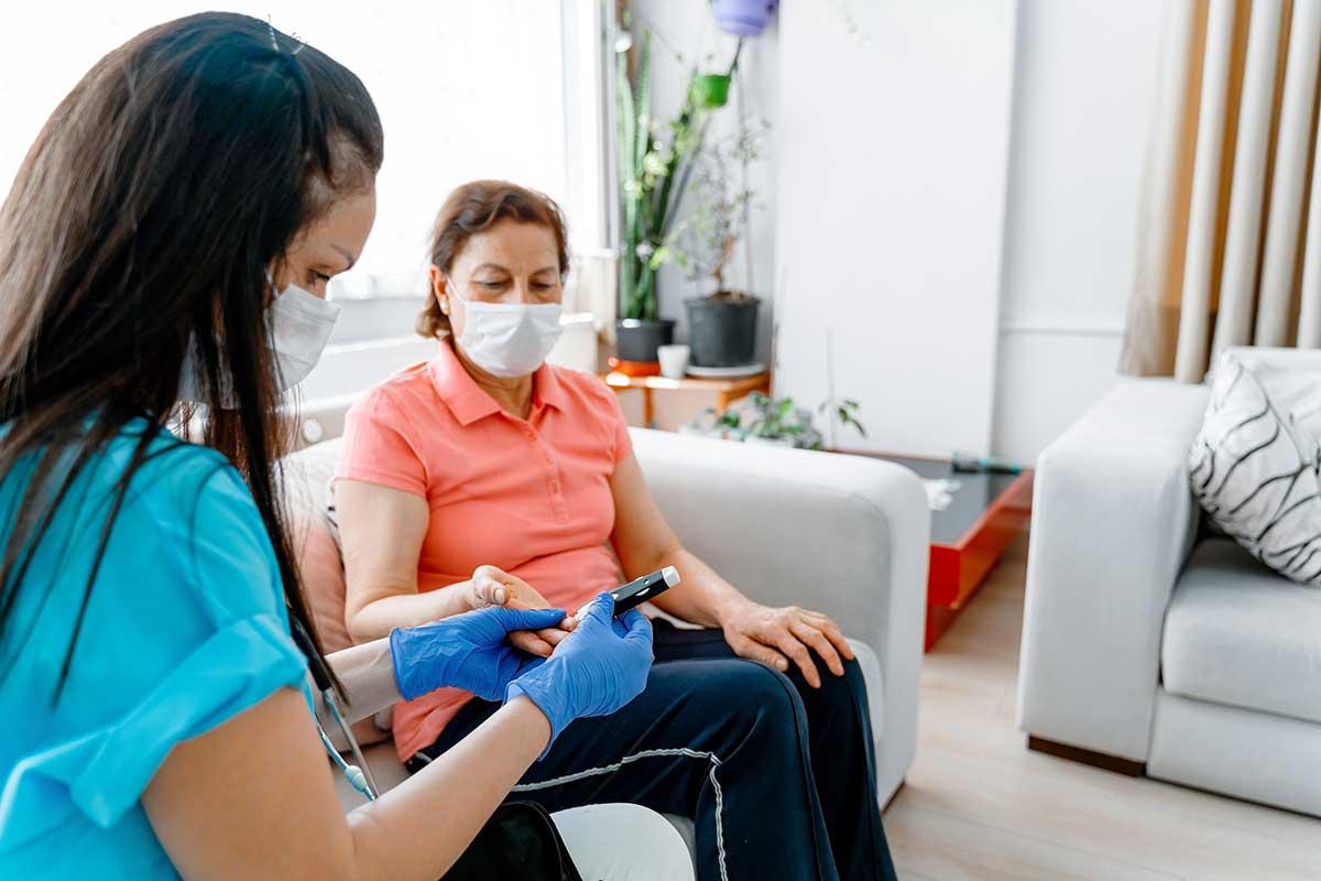 Un trabajador de salud ayuda a un paciente con un control de glucosa en sangre durante una visita a casa.