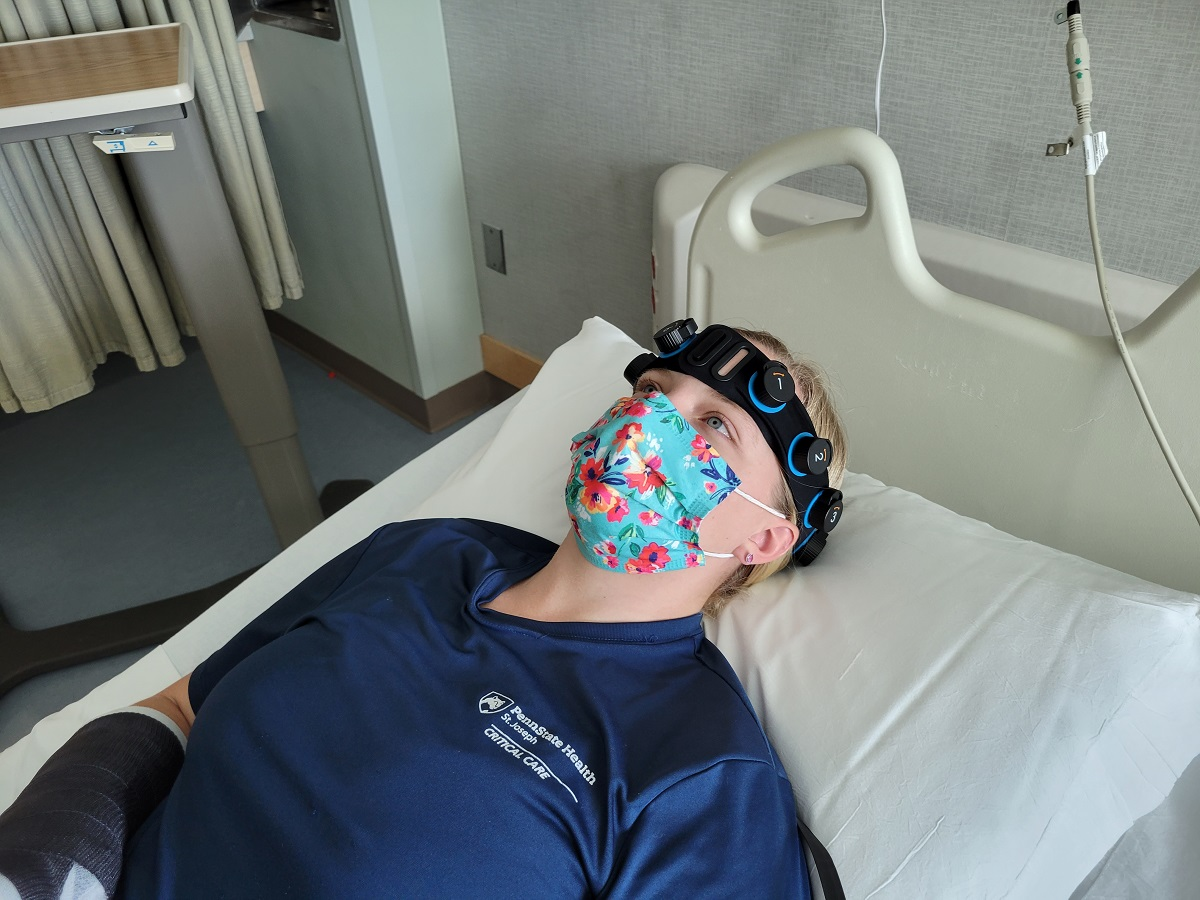A woman wearing a face mask lays on an exam table to demonstrate the Ceribell Rapid Response Electroencephalogram system. She is wearing scrubs and a headband with integrated electrodes.