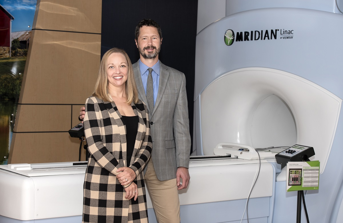 A man and woman stand in front of a Magnetic Resonance Imaging-guided linear accelerator.