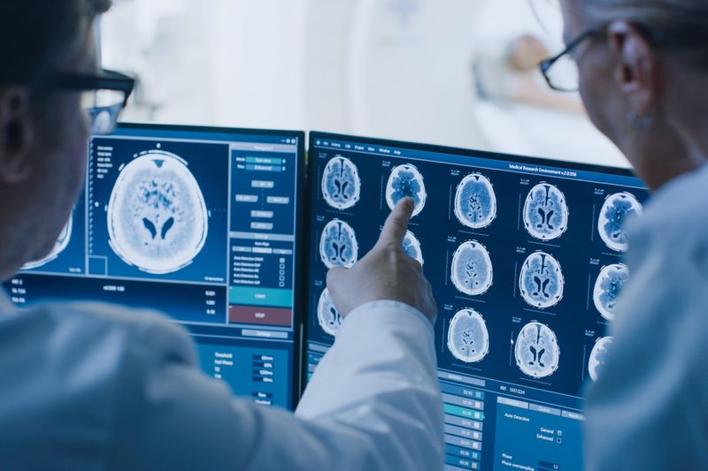 Two medical staffers in white coats look at screens containing several brain scan images. One of them points to a screen.