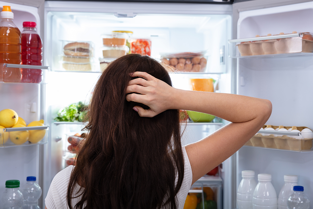 Confused Woman Searching For Food In An Open Refrigerator