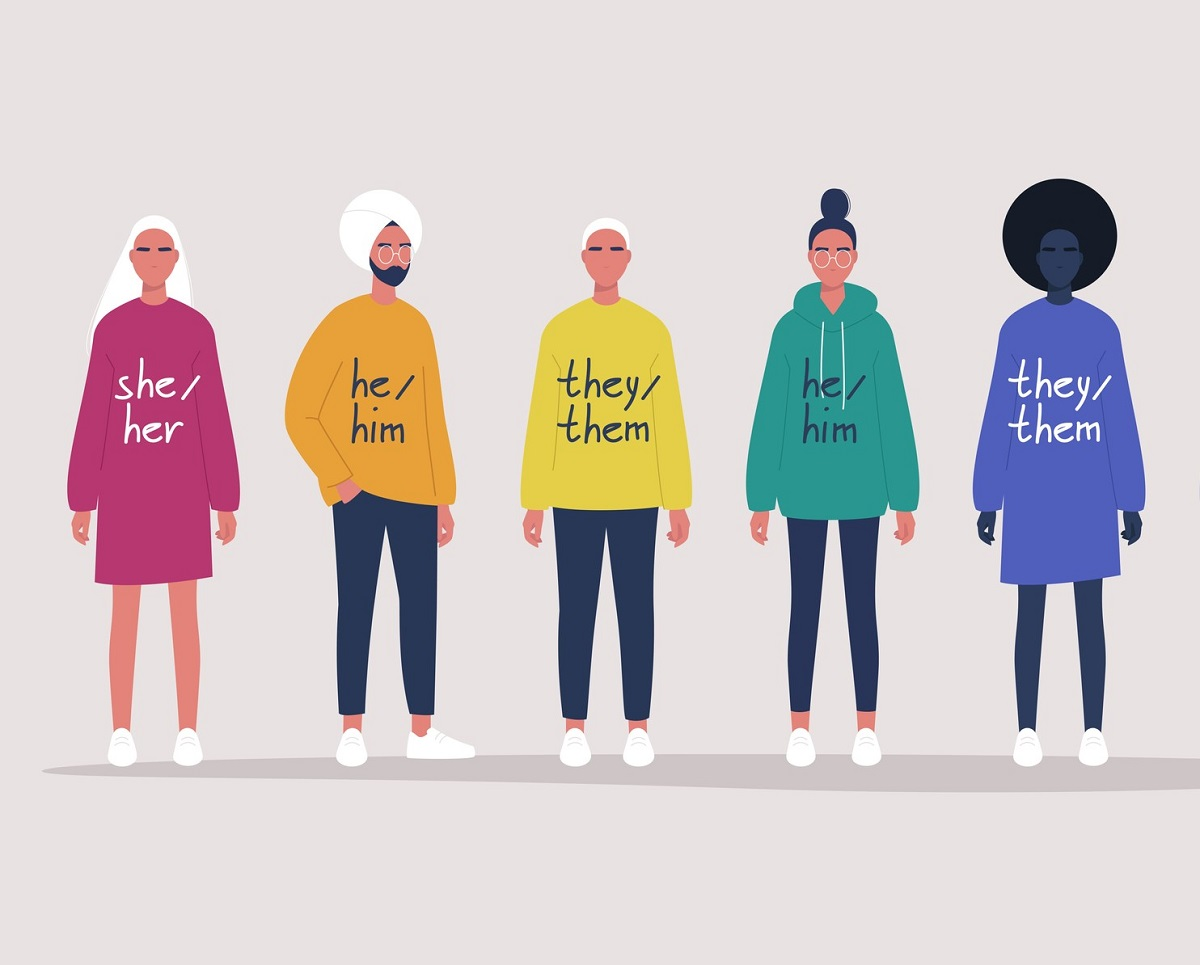 Illustration of a group of people lined up side by side with varying pronouns on the front of their shirts.