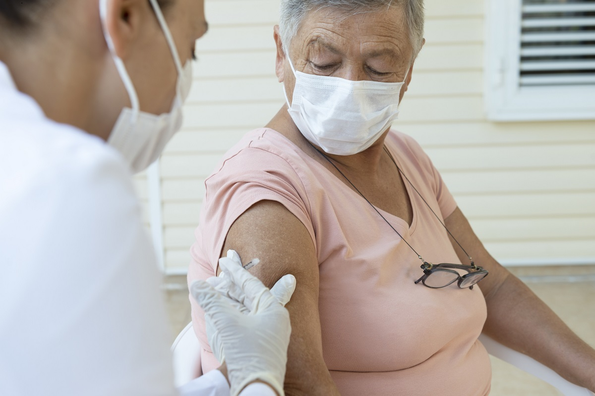 A woman wearing a mask receives an injection from a health care worker in gloves and wearing a mask.