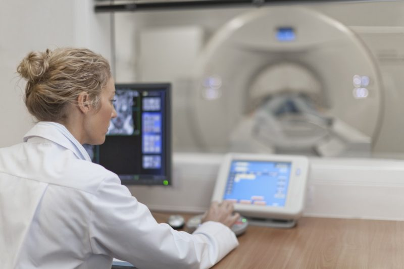 A doctor runs a CT scan on a patient.