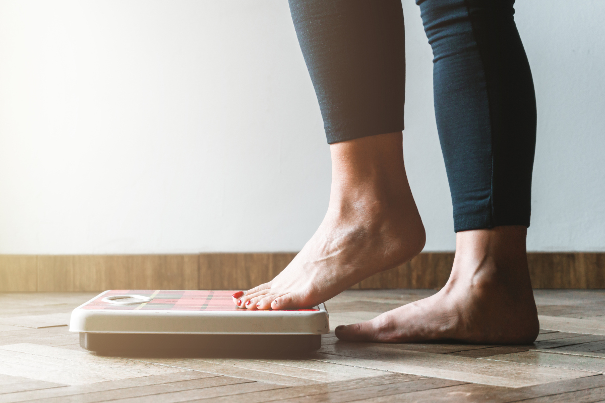 A woman steps onto a bathroom scale with her left foot first. Image is from the knees down.