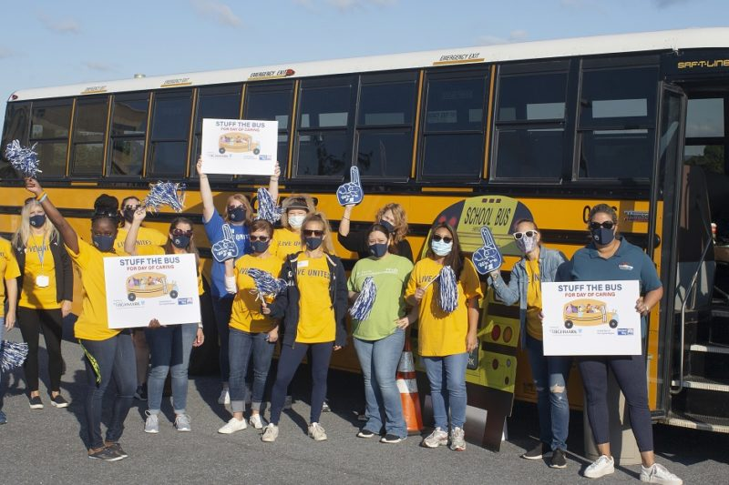 """A group of 14 women stand in front of a school bus holding """"Stuff the Bus"""" signs, pom-poms and foam fingers. Ten of them are wearing United Way T-shirts. Behind them is a Penn State Health pop-up tent."""