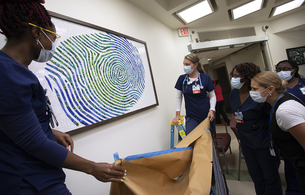 Women in surgical masks and scrubs gather around a framed picture of a fingerprint. Two of the women stand on a ladder and lower a large sheet of paper which had previously been used to cover the image.