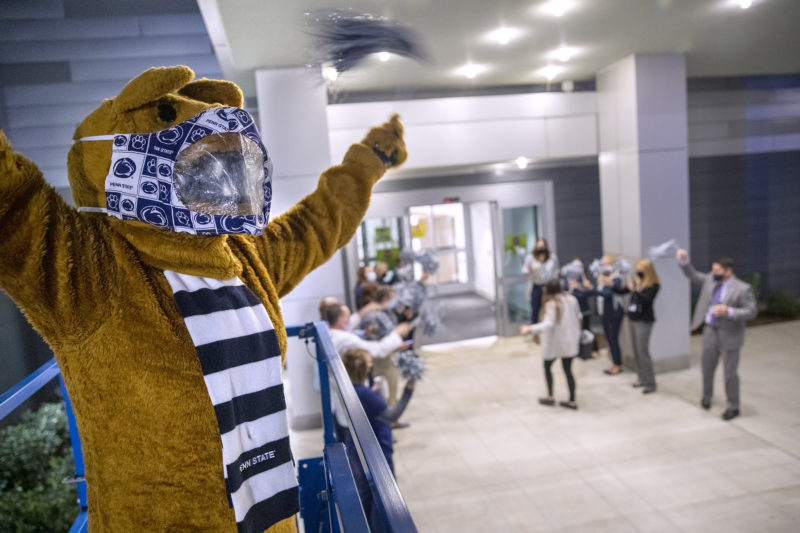 The Penn State Nittany Lion stands in the foreground, with several people in the background cheering as an individual walks through a doorway.