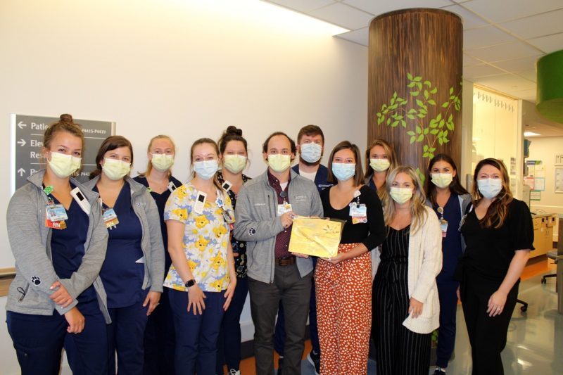 A dozen members of the Pediatric Intermediate Care Unit at Penn State Health Children's Hospital, wearing masks and scrubs, stand together in a hospital corridor while displaying an award certificate.