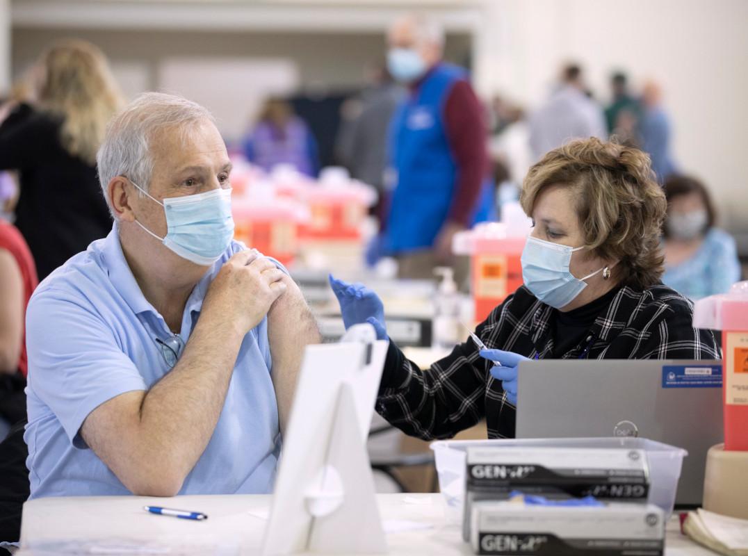 A nurse gives a man a vaccine in the arm