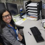 Margarita Biascochea smiles as she sits behind a desk with a computer monitor in front her. She has long hair, glasses and wears a zip-up sweat suit jacket over her shirt.