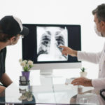 A patient and a doctor discuss cancer prognosis while viewing a chest x-ray.