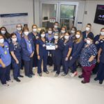 More than 20 staff on the 6th Floor Acute Care Unit, wearing scrubs and face masks, stand in a semi-circle in a hospital hallway. A woman in the middle of the group holds the award certificate in her hand.