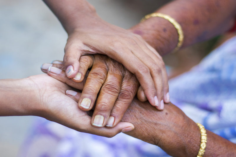 A close-up photo of two sets of adult hands with the one person's hands cradling the other person's hands to convey a sense of support.