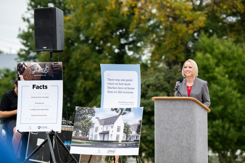 Dr. Jennifer Kraschnewski delivers a speech while standing at a podium at the groundbreaking ceremony for the first home being built as part of the Got Your 6 at Home initiative.